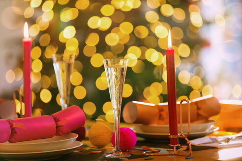Champagne flutes, candles and Christmas crackers on dining table - HOXF01862