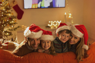 Portrait smiling family wearing Santa hats on living room sofa - HOXF01865