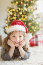 Portrait smiling girl wearing Santa hat on rug in living room with Christmas tree - HOXF01871