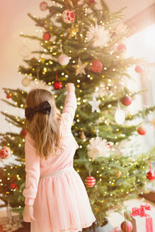 Girl in pink dress hanging ornaments on Christmas tree - HOXF01880