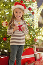 Portrait smiling girl in Santa hat holding gift in front of Christmas tree - HOXF01886