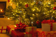 Gifts with red bows under illuminated Christmas tree - HOXF01889