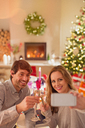 Smiling couple drinking champagne and taking selfie at Christmas dinner table - HOXF01913