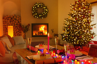 Ambient Christmas dinner table in living room with fireplace and Christmas tree - HOXF01916