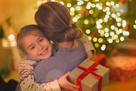 Smiling daughter with Christmas gift hugging mother - HOXF01922
