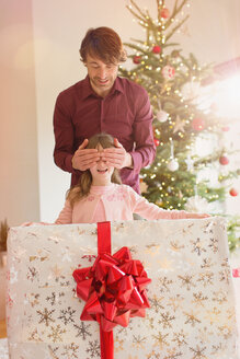 Father covering eyes of daughter holding large Christmas gift - HOXF01928