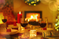 Red wine and candles on ambient Christmas table in front of fireplace - HOXF01937