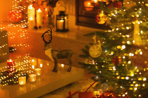 Reindeer decoration in ambient living room with candles and Christmas tree - HOXF01940
