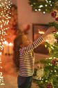 Girl hanging ornament on Christmas tree - HOXF01943