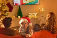 Portrait smiling girl in Santa hat watching TV with parents in Christmas living room - HOXF01964