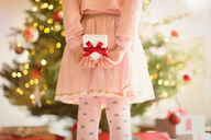 Girl in pink dress holding Christmas gift behind back in front of Christmas tree - HOXF01982