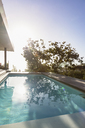 Tranquil sunny reflection of tree over lap swimming pool on luxury patio - HOXF01997