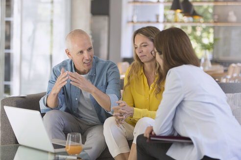 Financial advisor with laptop meeting with couple in living room - HOXF02015