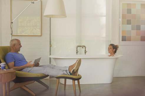 Husband with digital tablet relaxing, talking to wife in soaking tub in luxury hotel room - HOXF02018