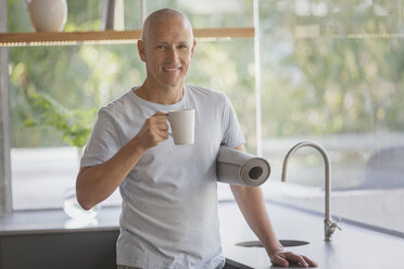 Portrait smiling mature man with yoga mat drinking coffee in kitchen - HOXF02042