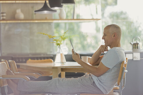 Mature man relaxing, using digital tablet with feet up at dining table - HOXF02048