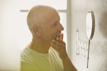 Mature man looking at skin in magnification mirror in bathroom - HOXF02051