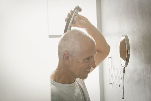 Mature man shaving head with electric razor in bathroom - HOXF02054