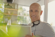 Portrait smiling mature man with headphones and digital tablet - HOXF02063