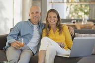 Portrait smiling mature couple using laptop on sofa - HOXF02069