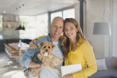 Portrait smiling mature couple hugging with dog in living room - HOXF02075