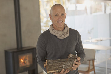 Portrait smiling mature man holding firewood in front of wood burning fireplace - HOXF02087