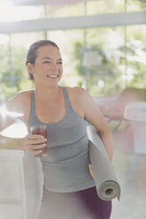 Smiling mature woman with yoga mat drinking healthy fruit smoothie - HOXF02090