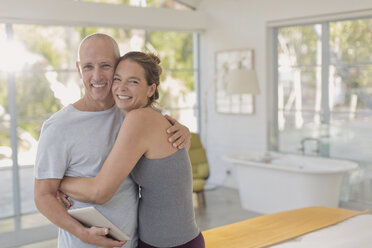 Portrait happy mature couple with digital tablet hugging in bedroom - HOXF02093