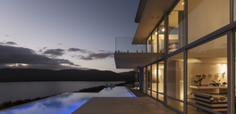 Tranquil modern luxury home showcase exterior with illuminated infinity pool and dusk ocean view - HOXF02096