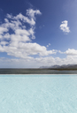 Sunny, tranquil infinity pool with ocean view under blue sky with clouds - HOXF02099