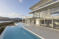 Sunny, tranquil modern luxury home showcase exterior with infinity pool - HOXF02102