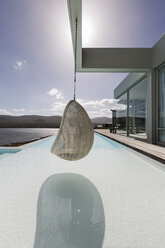 Hanging seat on sunny, tranquil modern luxury home showcase exterior with ocean view - HOXF02117
