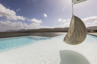 Sunny, tranquil luxury patio with infinity pool and hanging seat with ocean view - HOXF02126