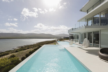 Sunny, tranquil modern luxury home showcase exterior with infinity pool and ocean view - HOXF02138