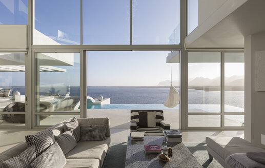 Sunny, tranquil modern luxury home showcase interior living room with patio and ocean view - HOXF02150