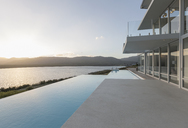 Sunny, tranquil modern luxury home showcase exterior with infinity pool and sunset ocean view - HOXF02153