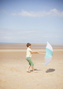 Wind pulling umbrella in hands of boy on sunny summer beach - HOXF02171