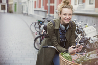 Portrait enthusiastic young woman on bicycle texting on city street - HOXF02210