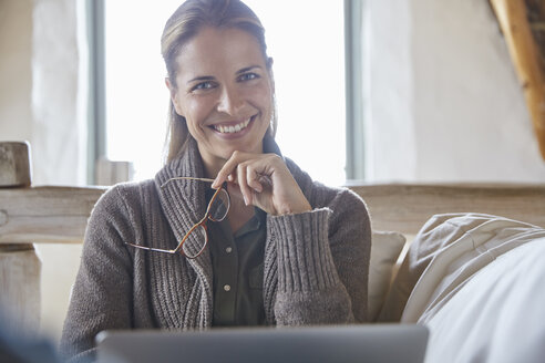 Portrait smiling woman with eyeglasses using laptop on sofa - HOXF02231
