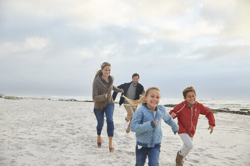 Playful family running on winter beach - HOXF02261