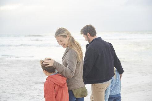 Smiling family walking on winter beach - HOXF02264