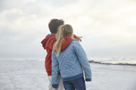 Affectionate brother and sister looking at winter ocean - HOXF02267