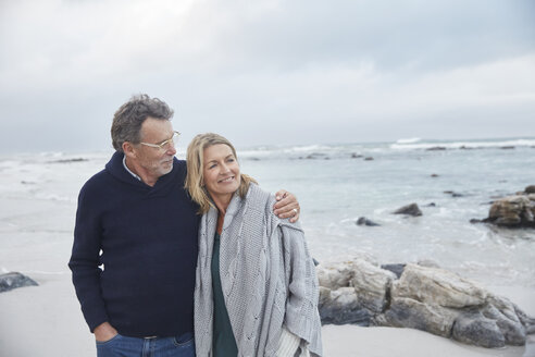 Affectionate couple hugging on winter beach - HOXF02273