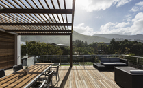 Sunny modern luxury home showcase exterior with wooden deck and mountain view - HOXF02288