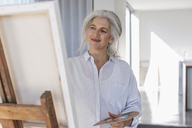 Smiling mature woman with palette painting at canvas on easel - HOXF02300