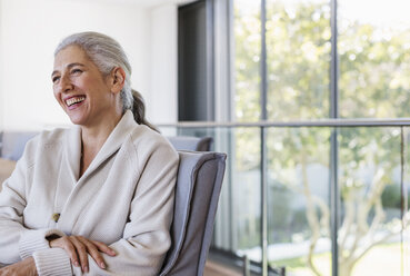 Mature woman laughing, looking away - HOXF02360