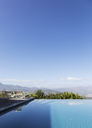 Tranquil luxury infinity pool with mountain view below sunny blue sky - HOXF02381