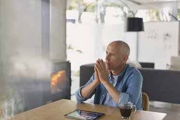Pensive man with digital tablet drinking coffee and looking away near wood burning stove fireplace - HOXF02423