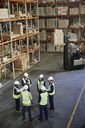 Manager and workers meeting in circle in distribution warehouse - HOXF02450