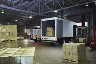 Trucks and cardboard box pallets at distribution warehouse loading dock - HOXF02453
